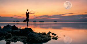 woman doing a yoga pose by the water with the moon above