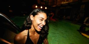 woman smiling on pool float in the dark