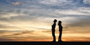 silhouette of couple standing back to back in front of sunset