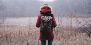 woman faces away from camera in misty, cold field wearing a red coat