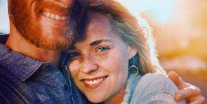 smiling woman hugging bearded man