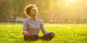 woman sitting cross-legged on the grass under the sun
