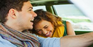 happy couple driving in a car