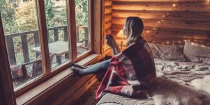 woman sitting on the bed looking out the window