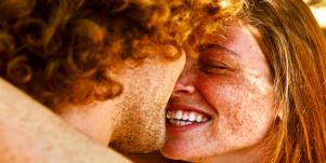 man and woman with freckles smiling kissing