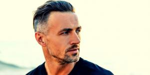 handsome man with chiseled features, slightly greying in his hair and goatee, looks over his shoulder