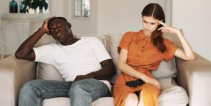 upset man and woman sitting on the couch