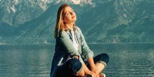 woman meditating on a lake