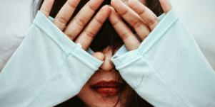 woman covering her face with hands