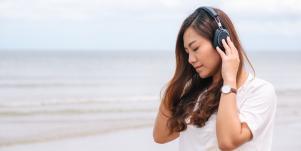 woman listening to music on beach