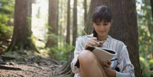 woman writing in notebook in the forest