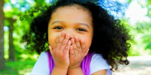 little girl with curly black hair covers her mouth