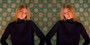 serious faced blonde haired woman wearing black sweater