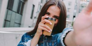woman holding a cup of coffee hiding her face