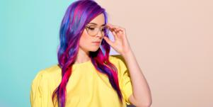 woman with purple hair adjusting her glasses