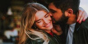 guy kissing a woman's check