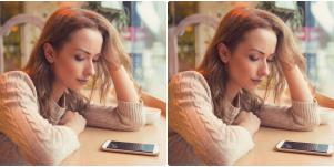 sad woman staring at phone on counter