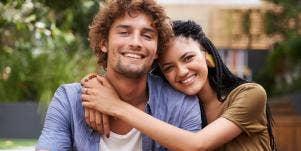 smiling woman hugging smiling man