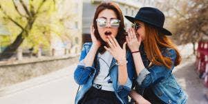 woman whispering gossip in another woman's ear