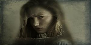 woman looking through broken glass