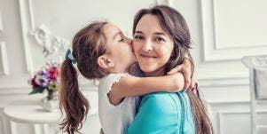 Daughter kissing smiling mom