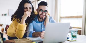 couple laughing staring at computer screen