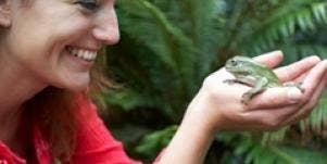 smiling woman holding frog princess prince metaphor