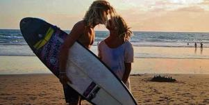 surfer couple kiss at the beach