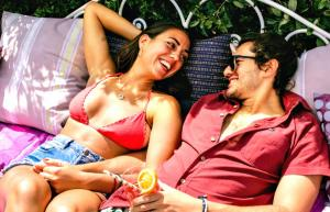 Brunette couple in their 20s lies back on an outdoor couch laughing and flirting